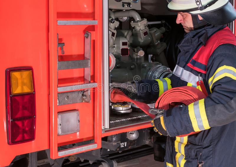 le-sapeur-pompier-dans-l-action-relié-un-tuyau-d-incendie-sur-le-camion-de-pompiers-63271841